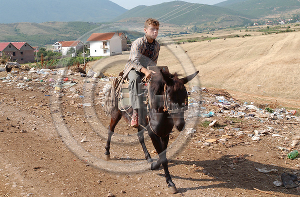 Liqenas-Korca/Korce-Albania - August 04, 2004---Improper waste disposal at the village of Liqenas, National Park of Prespa (triangle border lake of Albania, Macedonia, Greece), a boy on a horse passing by; project area of GTZ-Wiram-Albania (German Technical Cooperation, Deutsche Gesellschaft fuer Technische Zusammenarbeit (GTZ) GmbH); infrastructure-environment-people---Photo: Horst Wagner/eup-images