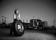A woman leans against a large truck tire in a parking lot with her 18 wheeler in the background.