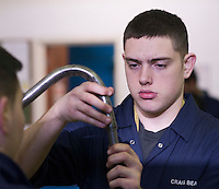 Student fitting one pipe inside an other, Motor Mechanics, Further Education College.