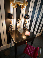 A dramatic black and white Regency-style stripe sets off a simple black painted writing table in the drawing room