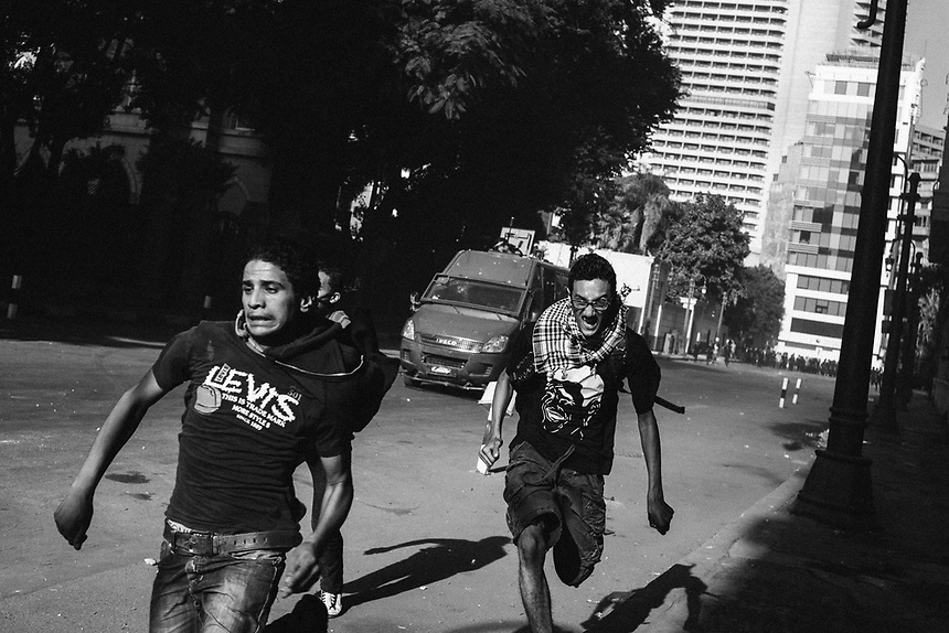 A group of young Egyptian protesters run away from an approaching riot police truck during violent clashes near Tahrir Square on September 13, 2012 in Cairo, Egypt.