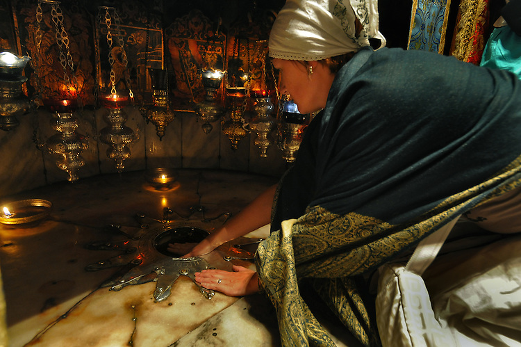A woman pilgrim at the Grotto of the Nativity, an underground cave located beneath the basilica, at the Church of the Nativity in Bethlehem, West Bank. The Grotto is believed to be the birth place of Jesus Christ. The exact spot is marked beneath an altar by a 14-pointed silver star.