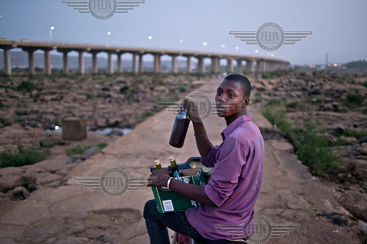 A man with some bottles near a Chinese built bridge spanning the River Niger. The bridge was opened in September 2011 and is the third crossing of the Niger in Bamako.