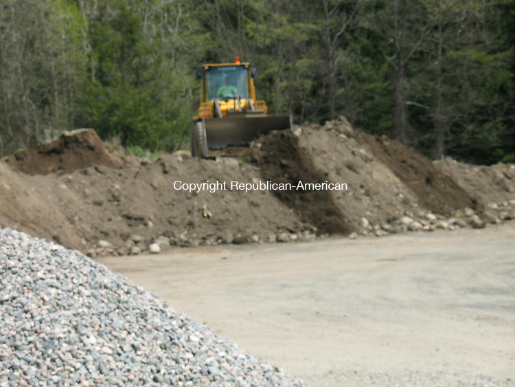 WASHINGTON, CT - 22 April 2010 - 042210RH01 - A town worker in Washington, Conn., moves a pile of soil farther from the Shepaug River Thursday after the town's wetland enforcement officer ordered the town to cease its dumping practices and restore the town-owned property at 16 Titus Road.