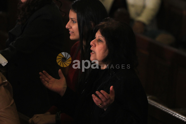 Worshippers pray during Christmas Eve Mass at Cairo s St. Mark s Cathedral, seat of the Coptic Orthodox Pope, in Cairo, Egypt, late Monday Jan. 6, 2014. Millions of Egyptian Christians on Monday thronged to churches across the mainly Muslim nation for Christmas Mass, held amid unusually tight security but with congregations filled with hope ahead of a key vote this month on constitutional amendments that enshrine equality and criminalize all types of discrimination. Photo by Mohammed Bendari