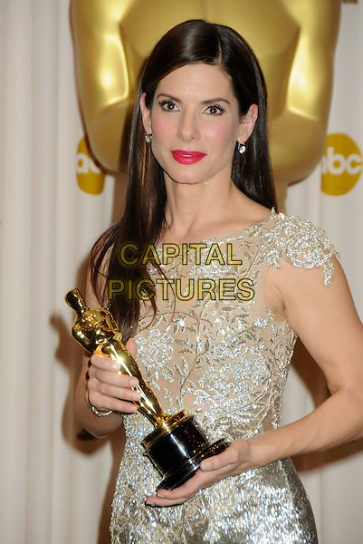 SANDRA BULLOCK.82nd Annual Academy Awards held at the Kodak Theatre, Hollywood, California, USA..March 7th, 2010.oscars half length silver gold beige silk satin pink lipstick dress winner trophy.CAP/ADM/BP.©Byron Purvis/AdMedia/Capital Pictures.