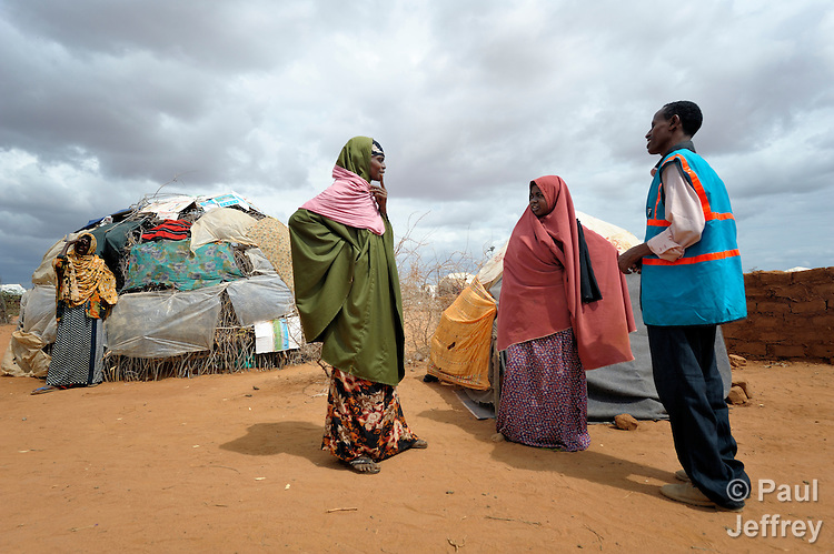 Adow Ibrahim Ali (right) and Fatuma Isaac Ar (second from right), Community Peace and Security Team members in the Dagahaley refugee camp, part of the huge Dadaab refugee complex in northeastern Kenya, talk with a woman about difficulties in the neighborhood. Already the world's world's largest refugee settlement, Dadaab has swelled in recent weeks with tens of thousands of recent arrivals fleeing drought in Somalia. The Lutheran World Federation, a member of the ACT Alliance, is manager of the camp, and sponsors the Community Peace and Security Teams in all three Dadaab camps. The teams, composed of volunteer refugees, mediate many ordinary conflicts, but refer violent crimes such as rape or murder to Kenyan police.