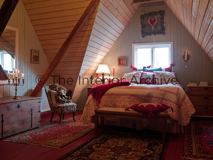 The sharply sloping, vaulted ceiling and rafters of this bedroom give it an unusual charm, especially when teamed with a cheerful floral print quilt and rugs
