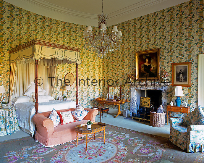 The master bedroom is furnished with a four-poster bed and chintz armchairs set against a patterned wallpaper