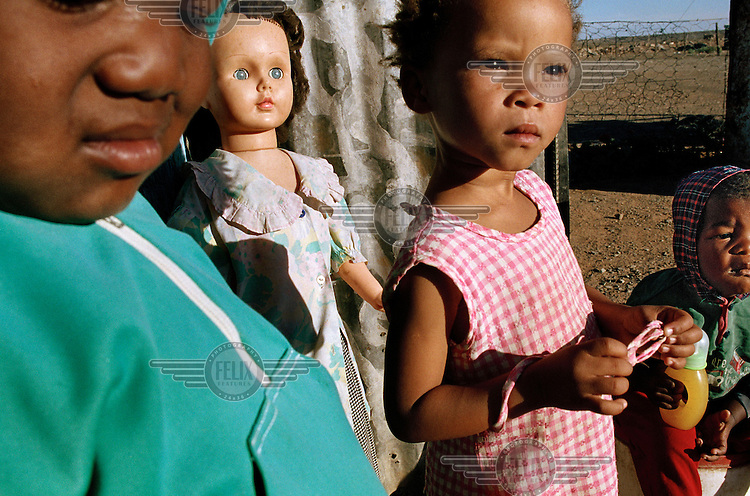 Children stand in front of a doll outside their hut in Victoria West.