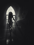 Sunlight lit silhouette of a beautiful nude woman back on a staircase in a house