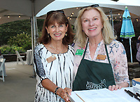 NWA Democrat-Gazette/CARIN SCHOPPMEYER Gayle Howard (left) and Tresha Jacky, botanical garden volunteers, welcome guests to Chefs in the Garden,