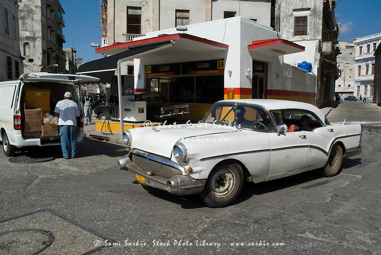 Classic American car passing by a gas station in Havana, Cuba.