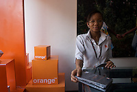 Sales staff at Orange.ug handing over a 3G data modem. Within the city limits wireless connections are rapidly becoming more popular than fixed wire broadband connections.