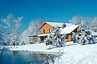 Cedar house near town reflected in private lake after fresh snowfall, midwest USA