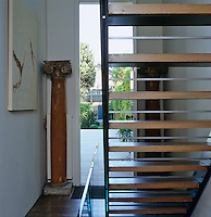 A modern glass and oak staircase leads from the entrance hall to the upper floors