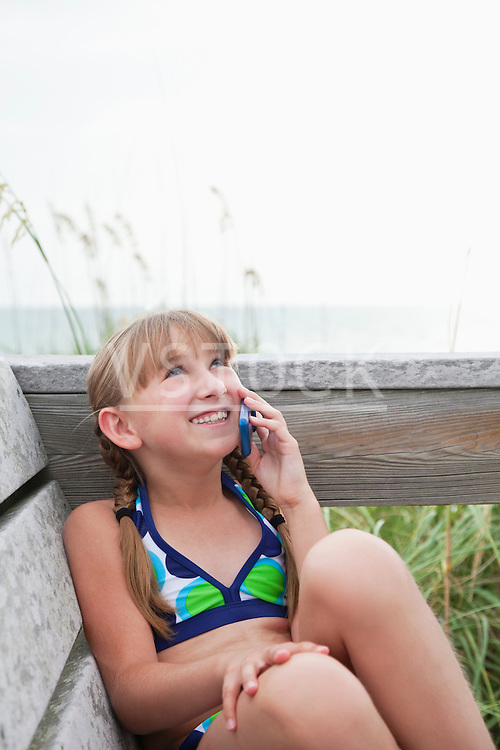 USA, Florida, St. Pete Beach, Smiling girl (8-9) talking on cell phone at beach