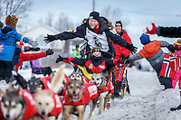 Ed Stielstra runs down Cordova Street giving high-fives to spectators during the Ceremonial Start of the 2016 Iditarod in Anchorage, Alaska.  March 05, 2016