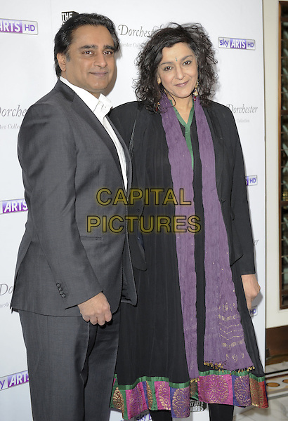 Sanjeev Bhaskar and Meera Syal.attended the South Bank Sky Arts Awards 2013, Dorchester Hotel, Park Lane, London, England..March 12th, 2013.half length black suit grey gray coat purple scarf married husband wife side.CAP/ROS.©Steve Ross/Capital Pictures
