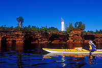 A kayaker paddles below Devils Island Lighthouse on Devils Island in the Apostle Islands National Lakeshore.