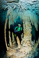 RX0846-D. scuba diver (model released) explores a freshwater-filled cavern accessible via a cenote (a sinkhole) in the jungle. This underground chamber is richly decorated with beautiful stalactites, stalagmites and columns, delicate limestone formations called speleothems created over millions of years. Riviera Maya, Yucatan Peninsula, Mexico.<br /> Photo Copyright &copy; Brandon Cole. All rights reserved worldwide.  www.brandoncole.com