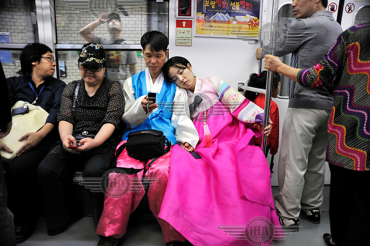 Couple dressed in traditional costume on a National Public Holiday travel on the underground train in central Seoul.