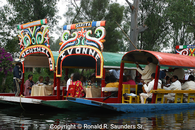 """[UNESCO WORLD HERITAGE SITE]<br /> <br /> TWO SEPARATE GROUPS of DINERS are ENTERTAINED by MUSICIANS in a LONE GONDOLA.<br /> <br /> Xochimilco is one of the sixteen boroughs within Mexican Federal District. Today,the borough consists of eighteen neighborhoods along with fourteen villages that surround it. While the neighbhoods are somewhat in the geographic center of the Federal District, it is considered to be """"south"""" and has an identity separate from the historic center of Mexico City. Xochimilco is best known for its canals, which are left from what was an extensive lake and canal system that connected most of the settlements of the Valley of Mexico. These canals, along with artificial islands called chinampas, attract tourists and other city residents to ride on colorful gondolas called<br /> """"trajineras"""". Its Hispanic past, has made Xochimilco a World Heritage Site."""