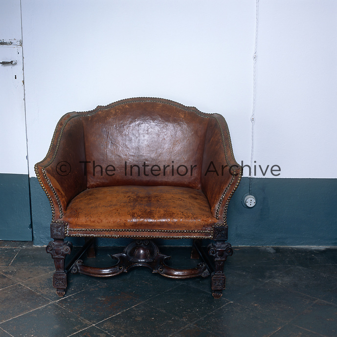 An antique brown leather seat is placed against a whtie and blue wall.