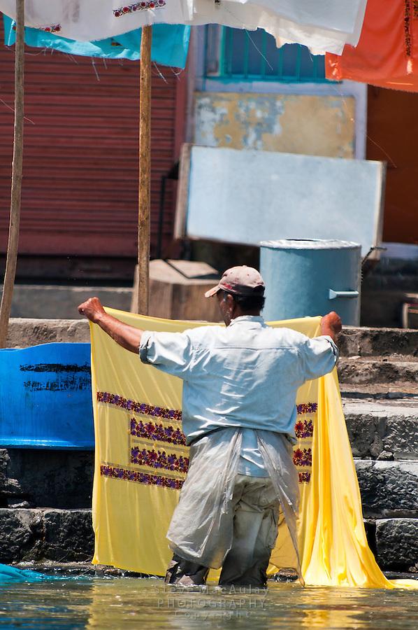 Kashmiri man washing laundry along the banks of Dal Lake, Srinagar, Kashmir, India.