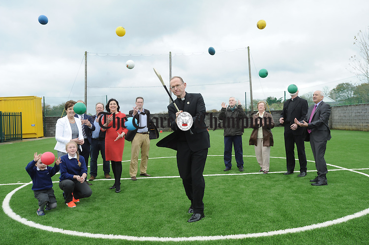 Bishop of Killaloe Fintan Monahan pucks out a sliotar at the official opening of the new pitch and building extension on the 50th anniversary of Toonagh NS. Looking on are pupils, Ava Sanders and Emily Whelan, Colette Crowe, former BOM member, Donnchadh Kelleher, Principal, Dave Whelan, builder, Marie Slattery, chairperson of the BOM, Mike Flynn and Jude Mc Kenna of Hassett Leyden, Mary Marrinan, former teacher, Fr Pat O Neill, PP and Joe Carmody, former principal. Photograph by John Kelly.