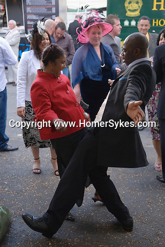 The Vodaphone Derby Day Horse Racing. Epsom Downs, Surrey, England 2007. Couple dancing at the end of the days racing.