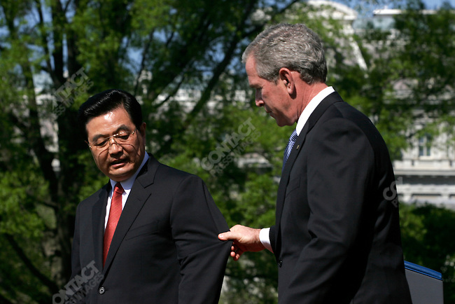 President George W. Bush (and wife Laura) greet the Premier of China, Hu Jin Tao, and his wife at an official White House welcome as part of a state visit.  Hu and Bush shake hands in the Oval Office of the White House.  Washington, D.C. April 20, 2006.