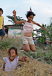 Children play by jumping into piles of rice chaff in the village of Dong in northern Cambodia.