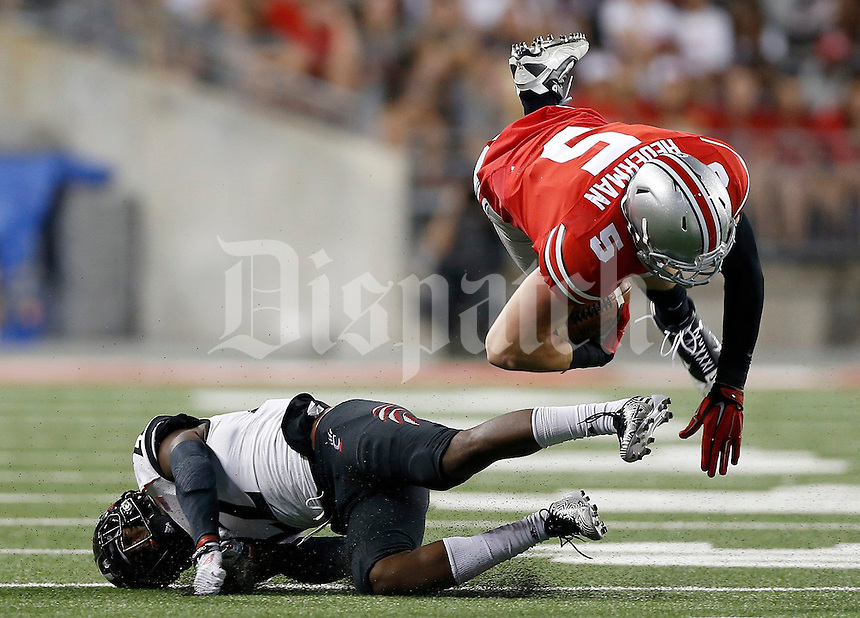 Ohio State Buckeyes tight end Jeff Heuerman (5) gets flipped by Cincinnati Bearcats safety Zach Edwards (22) during the third quarter of Saturday's NCAA Division I football game at Ohio Stadium in Columbus on September 27, 2014. (Columbus Dispatch photo by Jonathan Quilter)