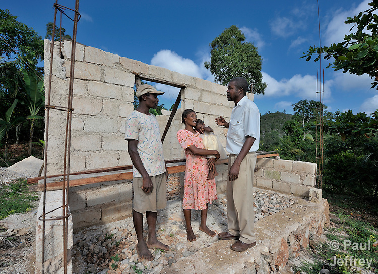 Paul Prevost, right, the co-founder of Haitian Artisans for Peace International (HAPI), talks with a family in the Haitian village of Mizak. HAPI is helping the family build a new house.
