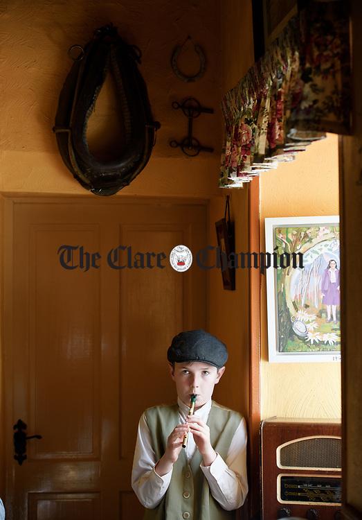 Ciaran Mc Carthy playing tin whistle during a cultural visit to The Rambling House in Kilmurry Mc Mahon by pupils of Labasheeda National School. Photograph by John Kelly.