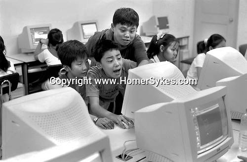 "The Peoples Republic of China. Shanghai. 2000.   Young Pioneers at an after-school club school enjoying a computer class. Known as "" Childrens Palaces"" there are thirteen of these arts and recreation centres in Shanghai.  Each year some 250,000 children under 16 attend classes in dance, music, crafts, calligraphy - and computers."