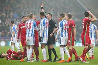 Referee Michael Oliver shows Huddersfield Town's Florent Hadergjonaj the yellow card for a challenge on Swansea City's Ki Sung-Yueng<br /> <br /> Photographer Alex Dodd/CameraSport<br /> <br /> The Premier League - Huddersfield Town v Swansea City - Saturday 10th March 2018 - John Smith's Stadium - Huddersfield<br /> <br /> World Copyright &copy; 2018 CameraSport. All rights reserved. 43 Linden Ave. Countesthorpe. Leicester. England. LE8 5PG - Tel: +44 (0) 116 277 4147 - admin@camerasport.com - www.camerasport.com