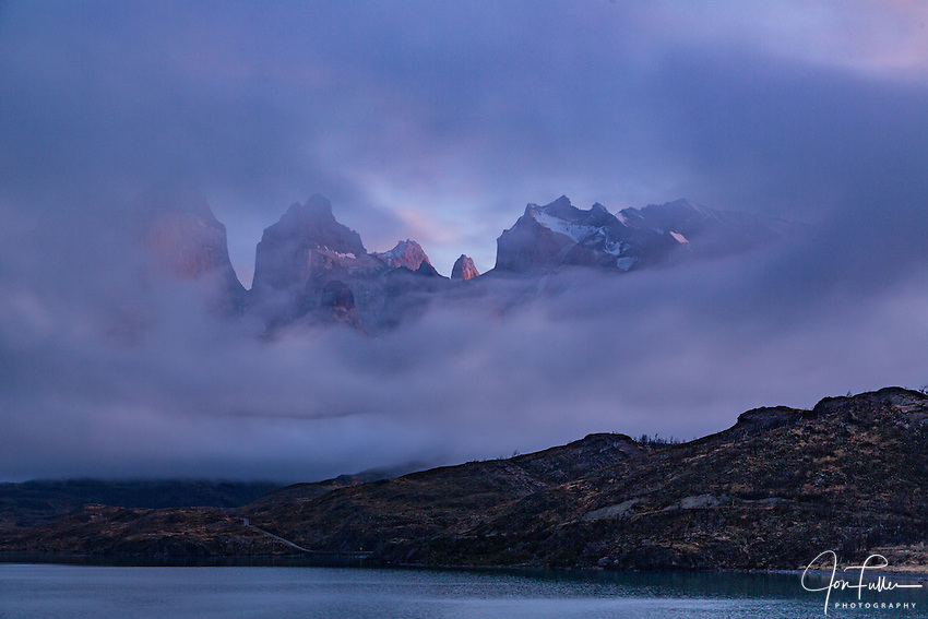 The Cuernos del Paine and Monte Almirante Nieto appear through a hole in the clouds.  Torres del Paine National Park in Patagonia, Chile.  A UNESCO World Biosphere Reserve.
