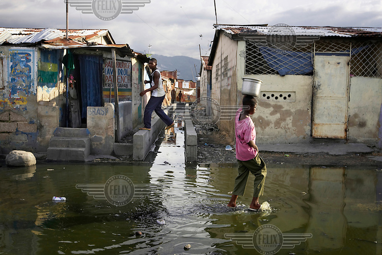 A boy steps over an open sewer as another boy carries a pot on his head while wading through a street that has been flooded by the sewer.