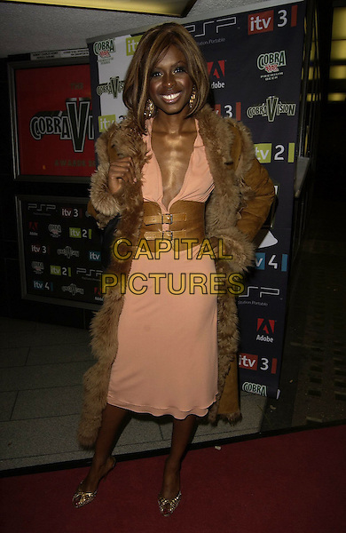 JUNE SARPONG.At the CobraVision Film Awards, Curzon Mayfair, .London, England, April 24th 2006..full length brown leather waist cincher belt buckles coat fur lined peach coral dress low cut plunging neckline skinny ribs bones sticking out.Ref: CAN.www.capitalpictures.com.sales@capitalpictures.com.©Can Nguyen/Capital Pictures