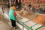 Washington DC, Food, fresh fish and shellfish market on Maine Ave, selling Chesapeake Bay blue crab and various fish, such as fillet of red snapper, all fresh and live off the boats.  Photo shows couple buying fillet at market..Photo  wash99324-70658..Photo copyright Lee Foster, www.fostertravel.com, lee@fostertravel.com, 510-549-2202.