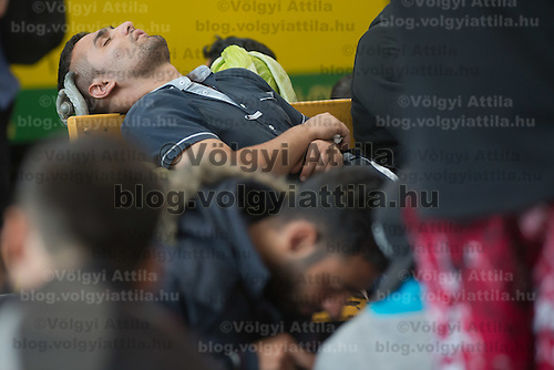 Illegal migrant sleeps on the platform as their family waits to board a train in hopes to leave for Germany at the main railway station Keleti in Budapest, Hungary on September 03, 2015. ATTILA VOLGYI