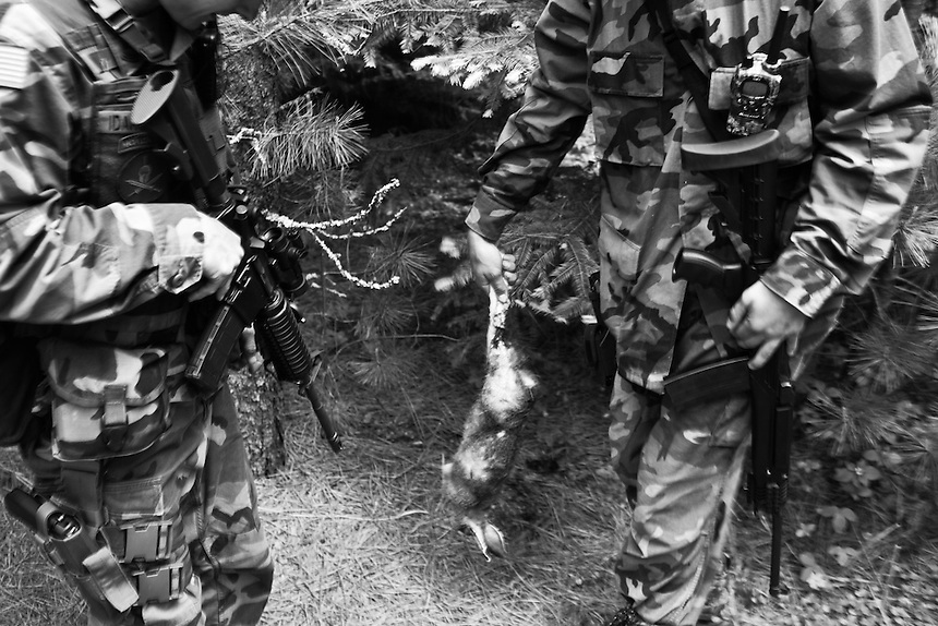 Members of the Idaho Light Foot Militia inspect a rabbit after they killed it while it crossed a road near their training camp in Priest Lake, Idaho...Initially they had planned on eating the rabbit with dinner, but soon found out from the battalion medic that it may contain harmful bacterias, and was later discarded.