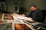 Artist Eric Bowman works on his current project  painting the cover of the premier edition for the  Saturday Evening Post magazine at his workstation at his studio in Tigard.