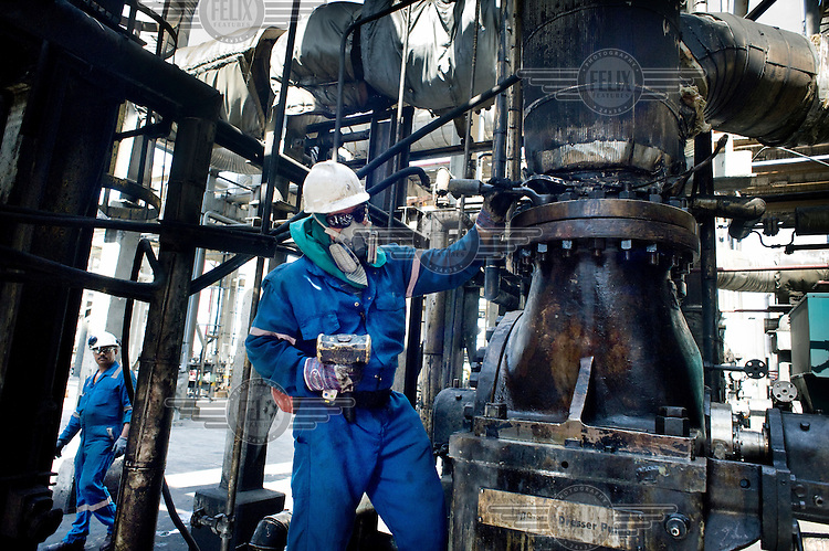 An oil worker tightens bolts on a part of the pumping mechanism at an oil refinery in Puerto la Cruz.