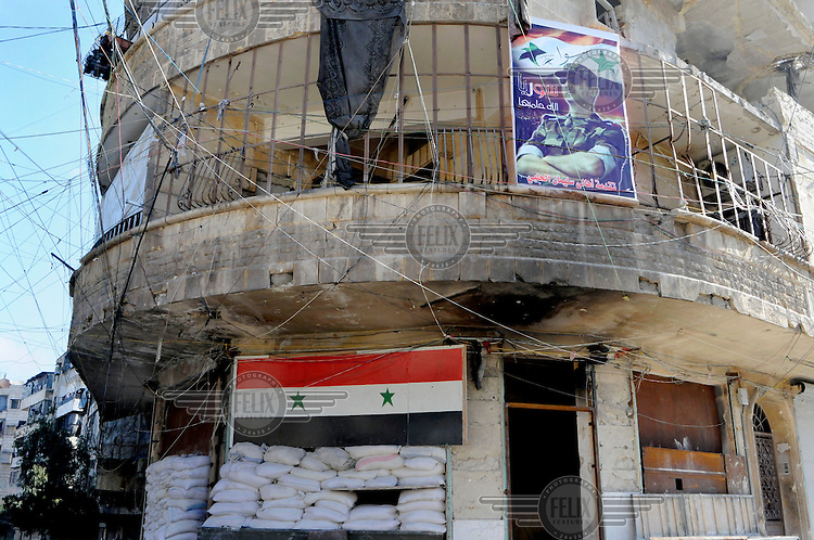 A Syrian flag and portraits of president Bashar al-Assad hang from a building in government controlled territory in the city centre.
