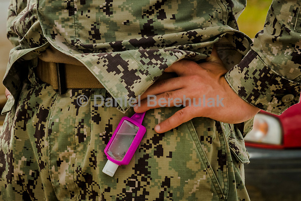 MONROVIA, LIBERIA - SEPTEMBER 30, 2014: Hand sanitizer hangs off the belt of one of the members of a team of U.S. Navy engineers working on preparing the ground for a 25-bed medical facility, they are building next to the airport in Monrovia on September 30, 2014 in Monrovia, Liberia. <br /> <br /> Daniel Berehulak for The New York Times