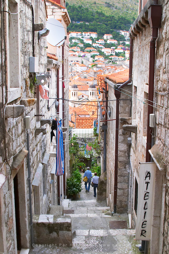 A steep street leading down from the city wall to the city and a view over rooftops roof tops Dubrovnik, old city. Dalmatian Coast, Croatia, Europe.