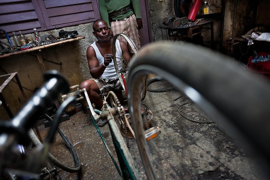 A Cuban service man fixes a bike wheel in the bicycle repair shop in Havana, Cuba, 10 February 2011.
